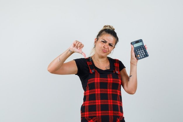 Woman in pinafore dress holding calculator, showing thumb down and looking disappointed , front view.