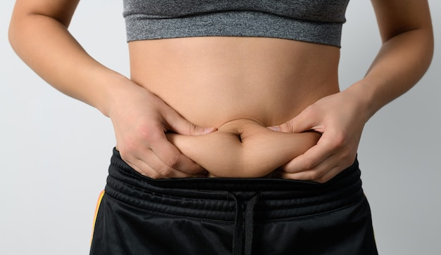 A woman pinches the excess fat on her belly with her fingers. on white background.