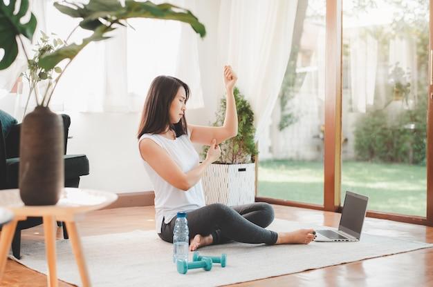 Женщина сжимает руку трицепс жирной дряблой кожи перед началом тренировки