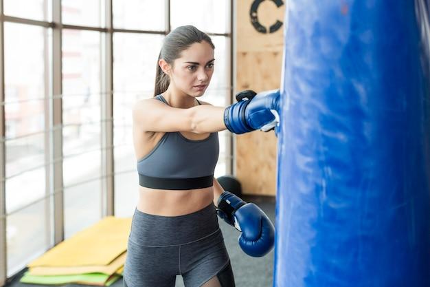 Woman pinching bag in gym