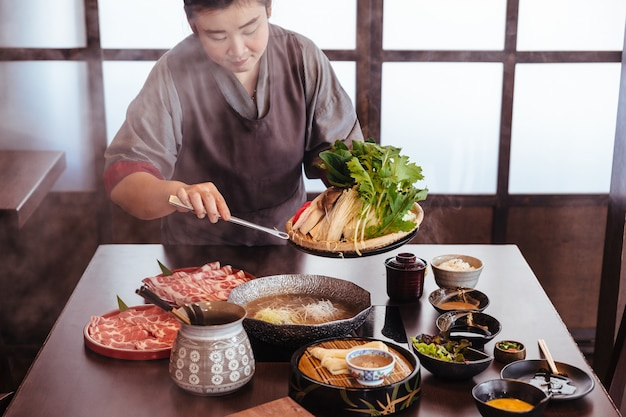 A woman pinching vegetables into hot pot