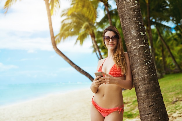 Woman in pink bikini leaning to palm tree holding phone