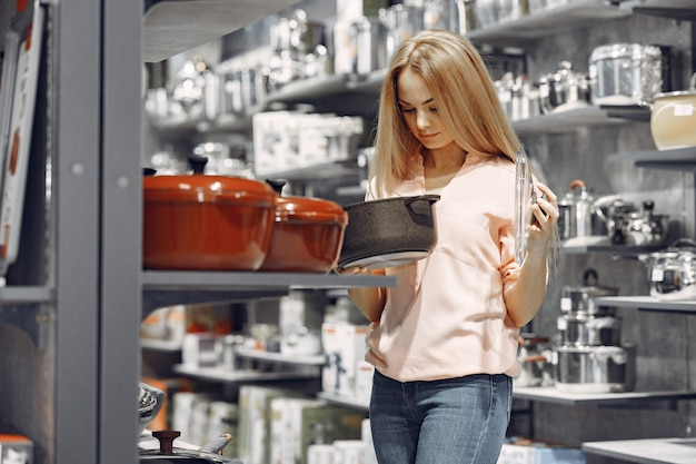 Woman in a pink blouse buys dishes in the store