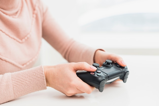 Woman in pink clothes playing game console