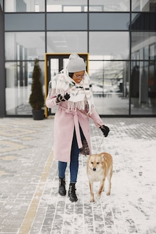 Woman in a pink coat, walking dog