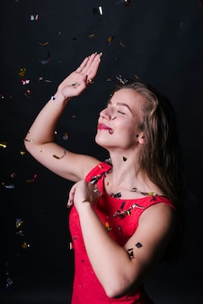 Woman in pink dress dancing under shiny spangles