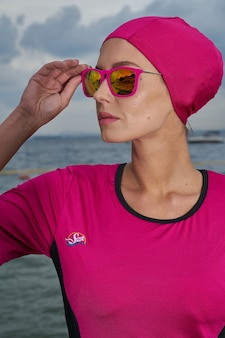 Woman in pink dress and pink headscarf and sunglasses