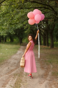 Woman in pink dress with pink balloons and wicker basket in green sunday park