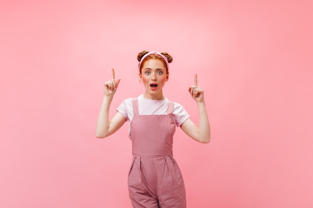 Woman in pink jumpsuit got idea. portrait of young redhead woman on pink background.