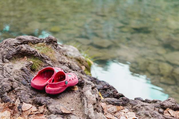 Woman pink plastic sandals over a rock near a lake