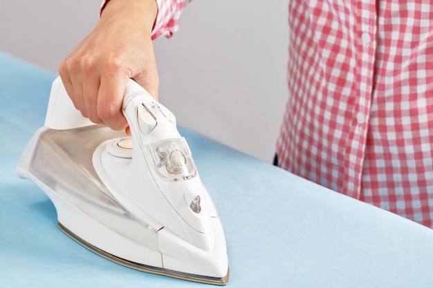 A woman in a pink shirt is ironing bed linen on an ironing board