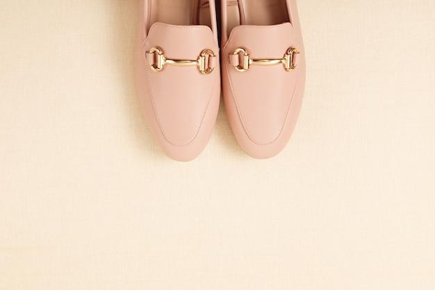 パステル調の背景の上の女性ピンクの靴