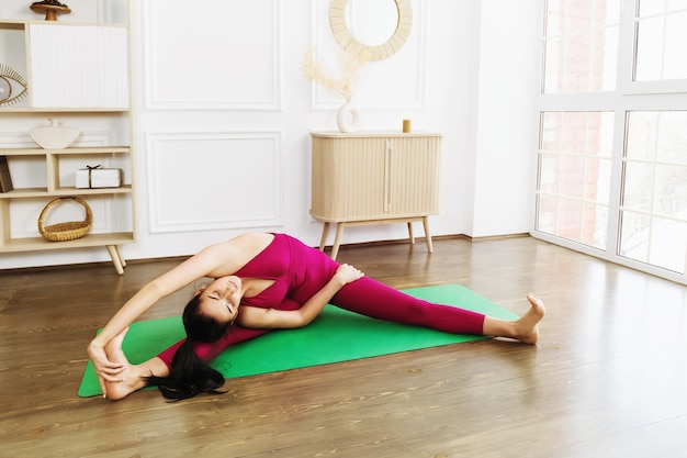 Woman in pink sportswear practicing yoga on a green rug at home performing an exercise with turning her head to the knee parivritta janu sirsasana