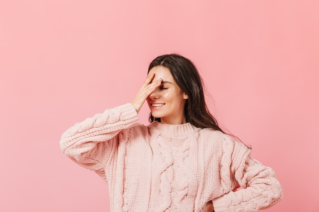 Woman in pink sweater posing on isolated background. funny girl with smile makes facepalm.