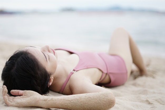 Woman in pink swimsuit lying on the sandy beach