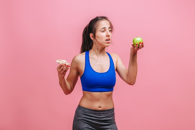 Woman on a pink wall holding a cake and an apple