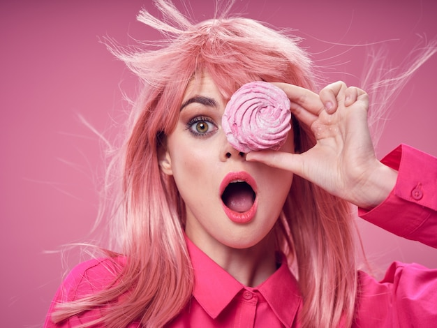 Woman in a pink wig, covering her eye with a cupcake
