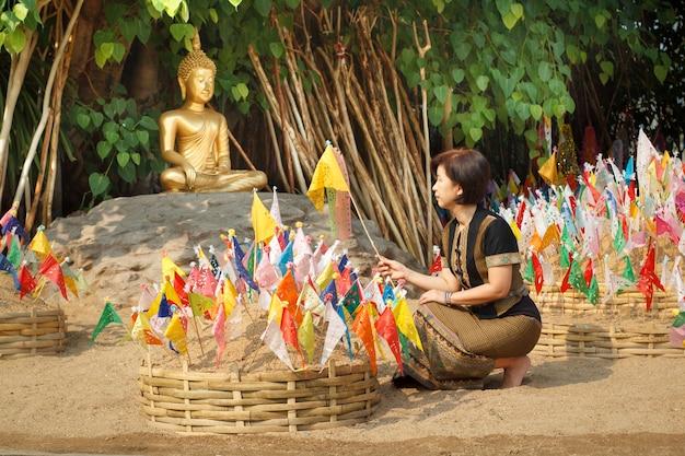 ソンクラーン祭りでチェンマイの寺院の砂の塔に伝統的な国旗を留めた女性