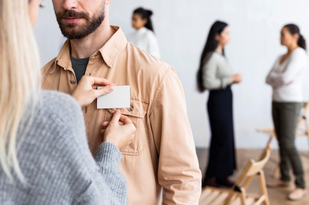 Woman pinning name tag on man's shirt at a group therapy session