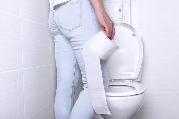 彼女の手に紙のロールでトイレの白い便器に下痢をしている女性の放尿