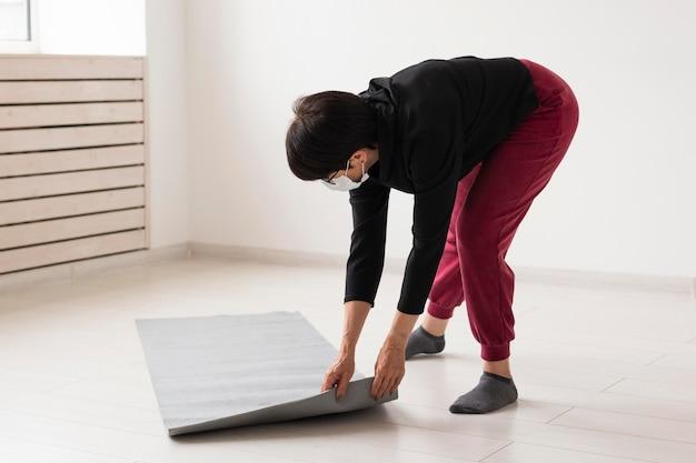床にフィットネスマットを置く女性