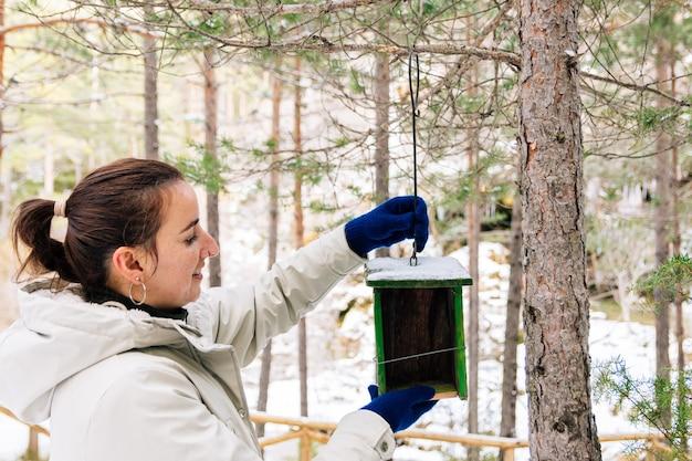 森の中に木の鳥の巣を置く女性。雪景色