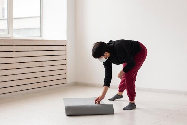 Женщина кладет коврик для йоги на пол