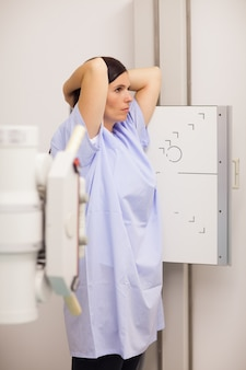 Woman placing her arms on her head while standing in front of a machine