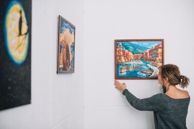 Женщина, размещающая живопись на стене