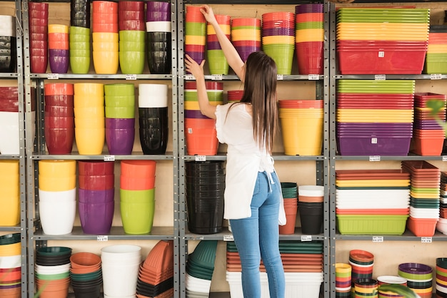 Woman placing stacked flowering pots in shelf
