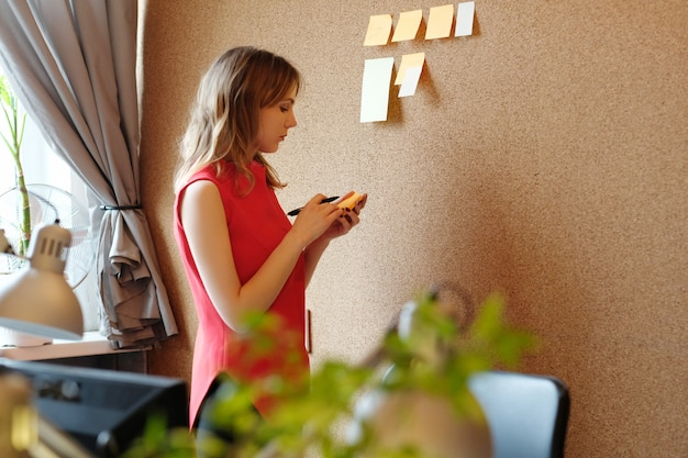 Woman placing sticky notes on a wall