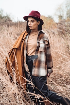 Woman in plaid coat, black fur pants and red hat walking on straw