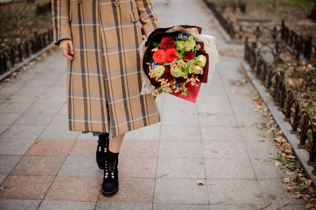 Woman in plaid coat walking with a bouquet of flowers on the alley