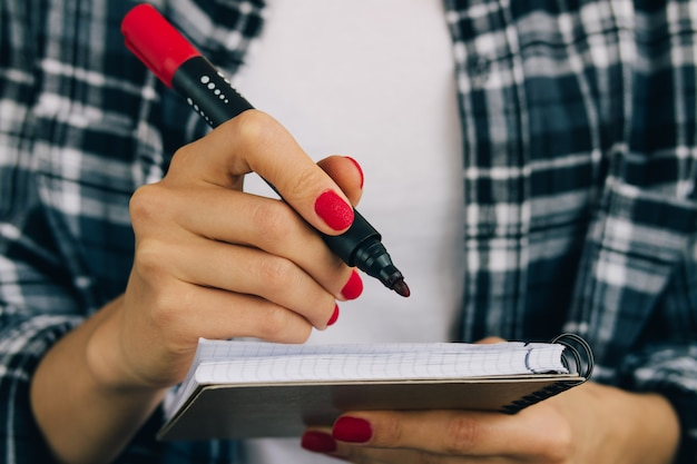 Woman in plaid shirt and red manicure felt pen writing in a notebook
