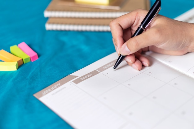 Woman planning agenda and schedule using calendar event planner