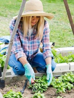 Женщина сажает в своем саду