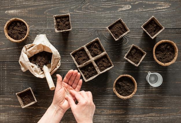 Женщина сажает саженцы в экологически чистые горшки, горшки на деревянном фоне, небольшую сумку с землей и садовой лопаткой и граблями