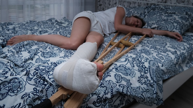 Woman in a plaster cast lies on the bed at home, crutches lie nearby.