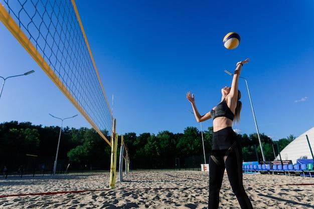 ビーチでバレーボールをめっきする女性