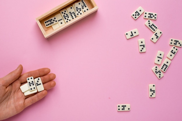 Woman play board game of dominoes on pink