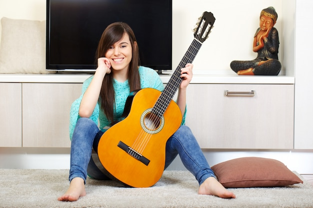 Woman play guitar at home