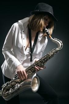 Женщина играет на саксофоне на черном фоне