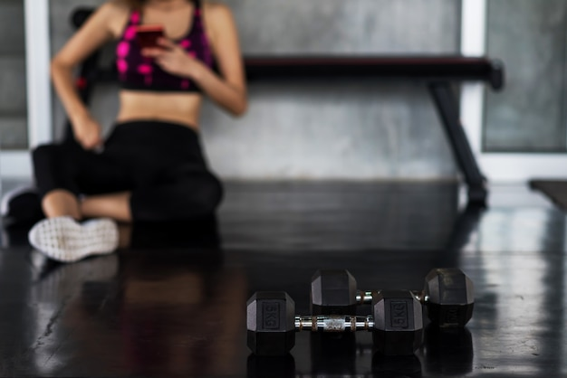 Woman play smart phone after workout dumbbell