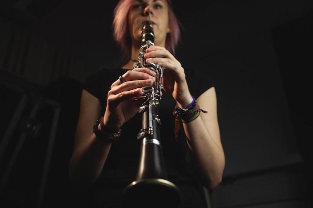 Женщина играет на кларнете в музыкальной школе