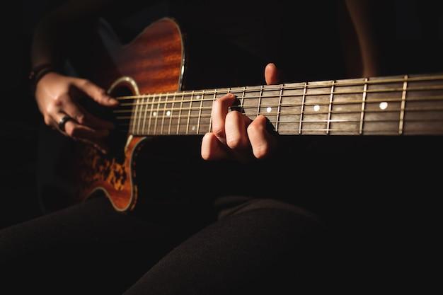 Женщина играет на гитаре в музыкальной школе