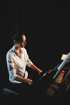 Женщина играет на пианино в музыкальной студии
