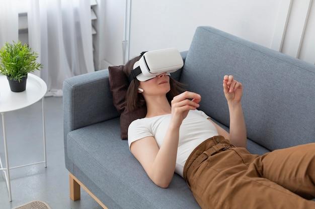 Vrゴーグルを使用しながらビデオゲームをプレイする女性