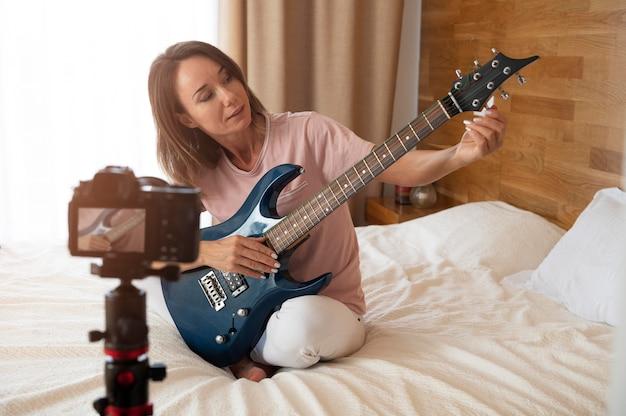 家でエレキギターを弾く女性
