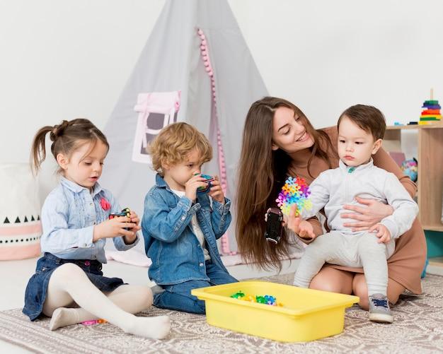 어린이와 장난감 집에서 노는 여자
