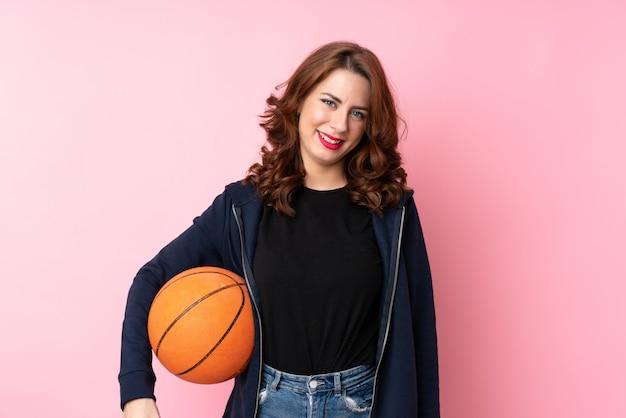 Woman playing basketball over isolated wall